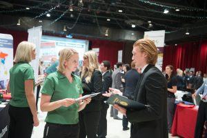 Illinois State students talks to a professional representative at a career fair