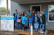 Volunteers and family stand in front of new home