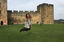 Hannah Lehman jumping in front of castle in Scotland