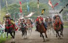 horses running on a track with people in traditional garb