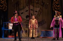 Three actors in colorful costumes on stage