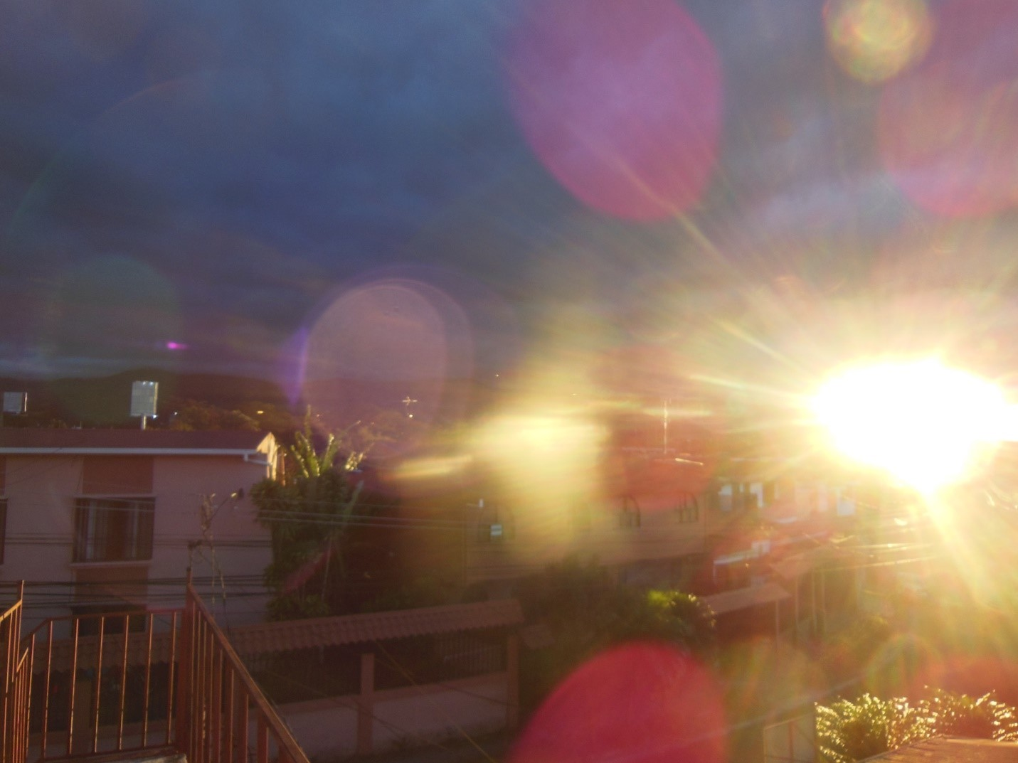 sunset with lens flare overlooking houses in Costa Rica