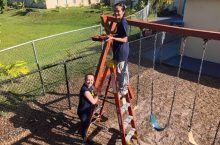 two students staining swingset