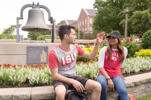 Two students talking while sitting in front of the Old Main Bell