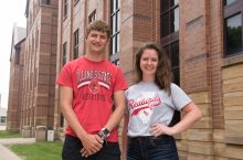 Dan Chastain and Claire Meyer pose in front of the State Farm Hall of Business