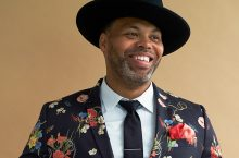 man wearing flowered jacket and black rimmed hat