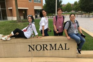 four people seated at a sculpture with the word Normal on it.