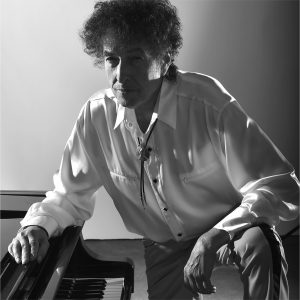 Bob Dylan leaning over a piano