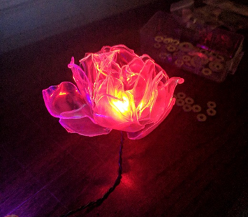 Flowers made of plastic cups and wire light up in St. Aubin's Windstorm
