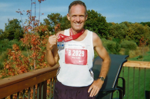 Runner holding medal after finishing race