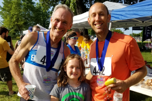 Two runners with a child, showing race medals