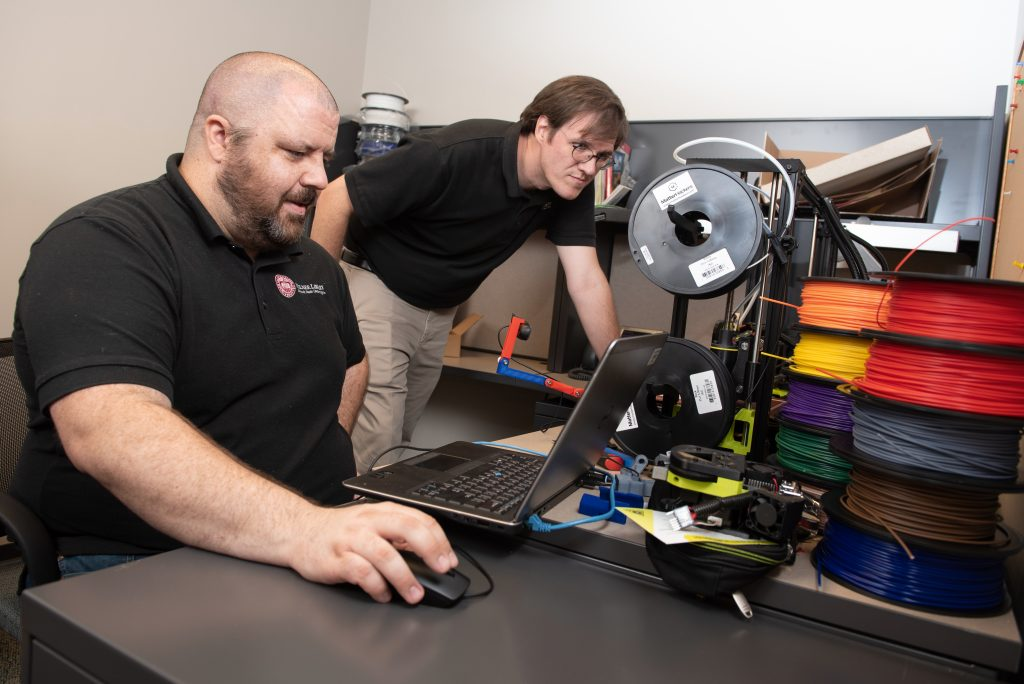 Library staff operates 3D printer.