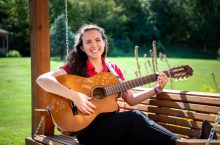 Illinois State University music therapy student Noelle Ortega playing guitar on a bench