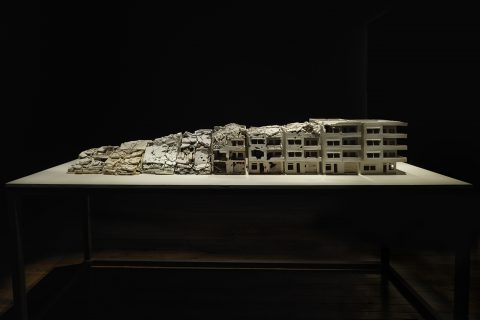Photograph of art installation by Alison Ruttan depicting a series of buildings in various states of destruction from complete destruction to fully intact.