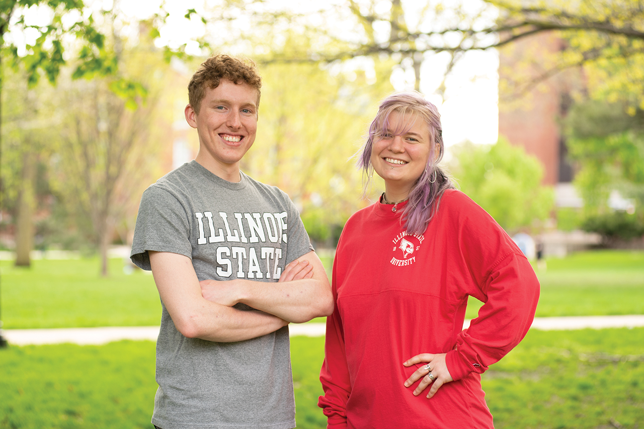 Male and female student standing on campus.