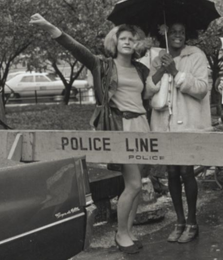 Two women behind a barrier that reads Police Line