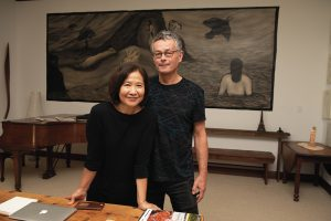 A husband and wife standing in front of a painting