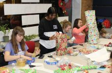 students wrapping holiday gifts