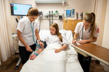 Nursing students Morgan Bangert (left), Elise Austin, and Kari Lalumandier participate in a training at the Nursing Simulation Lab.