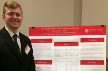 Jerome Sader standing next to his poster at University Research Symposium.