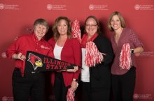 four people with ISU pom poms and a pennant