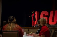 Alumna speaks to audience at a conference.