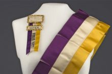 White dress form wearing a purple, white, and yellow National Woman's Party sash and ribbon reading