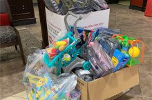 bags of toys in and around a collection box for Toys for Tots