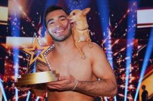 Man holds trophy and small dog
