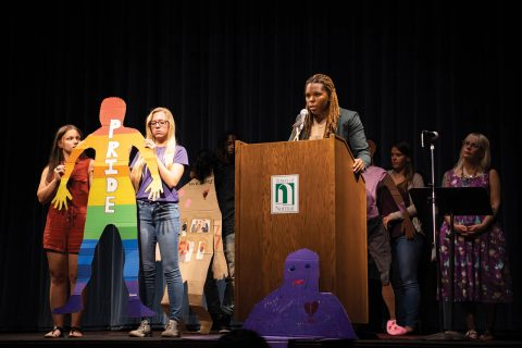 Students holding a cardboard cutout on stage, discussing domestic violence.