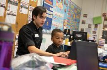 Young man tutoring a fourth grade student,