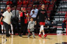 Man walking with little boy at basketball arena
