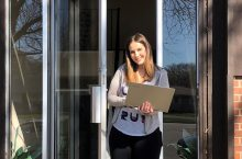 student standing outside an off-campus apartment