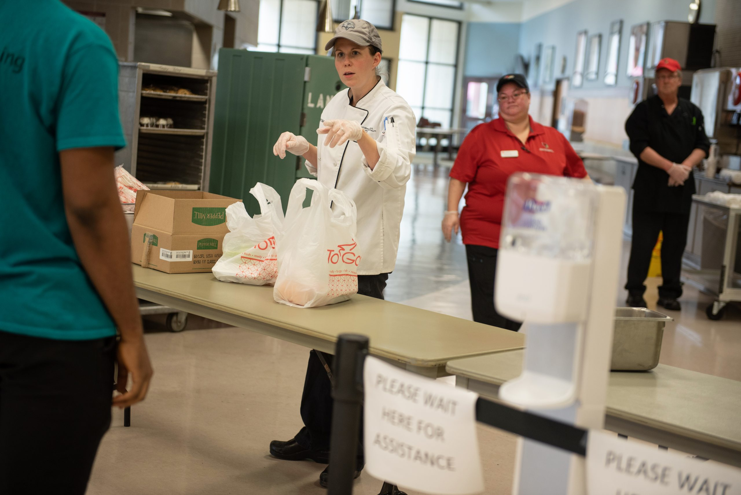 Event Management, Dining, and Hospitality Training Chef Ursula Ganci prepares to-go meals at Watterson Dining Commons for students who are still living on or near campus.