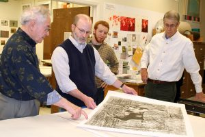 Four printmakers reviewing printed impressions