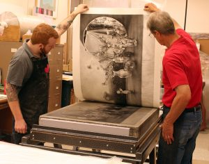 student and faculty pulling a print from a lithographic stone