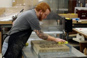 student sponging a lithographic stone