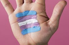 hand with the colors of the transgender flag painted on the palm