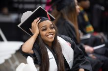 woman smiling and sitting on a chair in graduation regalia