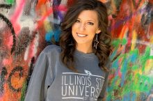 Student against a colorful wall wearing an ISU sweater