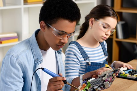 Two students putting together motherboards