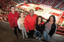 Avid Redbird basketball fans, the Jones family has attended the men's basketball Missouri Valley Conference Tournament for 19 years. They cheer on the team at home as well, and are pictured in Redbird Arena. They are, from left, Kevin Guidry-Jones '14, Abigail Jones, Michael Jones '92, Tracy Jones '03, and Ericka Jones-Carter '02. Redbird Arena
