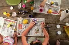 Youth making camp crafts with pain and newspaper