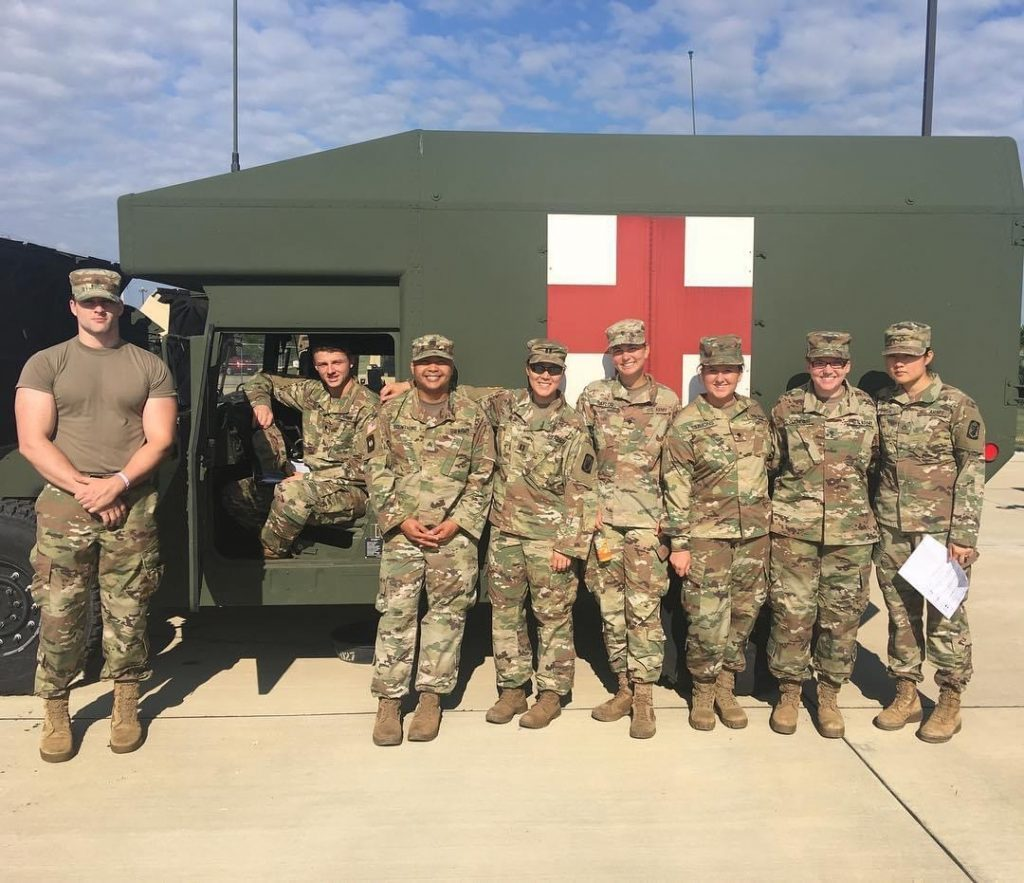 photo of Illinois Army National Guard posing in front of medic vehicle