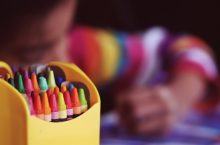 box of crayons in front of a child drawing