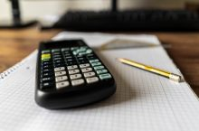 calculator and pencil sitting on desk