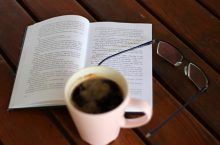 coffee, open book, and glasses on a wooden table