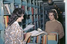 Two women compare books over a book cart in the stacks at Milner Library in 1962
