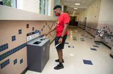 Male student places item in waste station