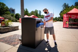 An Illinois State student uses a new waste station located outside Schroeder Hall.